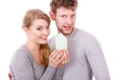 Οι νεολαίες το ζευγάρι που παρουσιάζει σύμβολο σπιτιών στοκ φωτογραφία