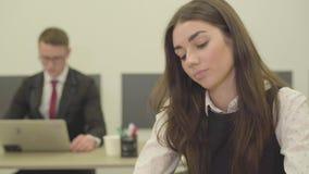 Οι νεολαίες τρύπησαν τη συνεδρίαση γυναικών στο πρώτο πλάνο στο γραφείο η εργασία συναδέλφων ανδρών της με το lap-top απόθεμα βίντεο