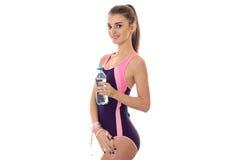 Οι νεολαίες που γοητεύουν τη λεπτή κυρία brunette στο μαγιό σωμάτων με το μέτρο δένουν με ταινία και μπουκάλι νερό στο χαμόγελο χ στοκ φωτογραφία με δικαίωμα ελεύθερης χρήσης