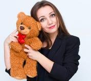 Οι νεολαίες που χαμογελούν το όμορφο κράτημα γυναικών teddy αντέχουν Στοκ εικόνα με δικαίωμα ελεύθερης χρήσης