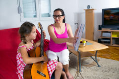 Οι νεολαίες το κορίτσι που έχει το μάθημα κιθάρων στο σπίτι Στοκ Φωτογραφίες