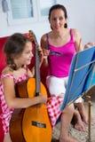 Οι νεολαίες το κορίτσι που έχει το μάθημα κιθάρων στο σπίτι Στοκ Φωτογραφία