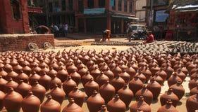 Οι νεπαλικοί λαοί διαμορφώνουν και στεγνώνουν τα δοχεία κεραμικής στο τετράγωνο αγγειοπλαστικής στοκ εικόνα