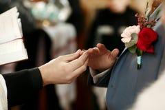 Οι νεόνυμφοι δίνουν με το γαμήλιο δαχτυλίδι στη γαμήλια τελετή στοκ εικόνες