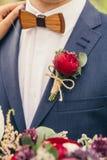 Οι νεόνυμφοι με τον ξύλινο τόξο-δεσμό και κόκκινος αυξήθηκαν μπουτονιέρα στο γάμο στοκ εικόνα