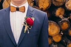 Οι νεόνυμφοι με τον ξύλινο τόξο-δεσμό και κόκκινος αυξήθηκαν μπουτονιέρα σε ξύλινο στοκ εικόνες