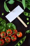 Οι ντομάτες κερασιών, chard και τα πράσινα μπιζέλια πλαισιώνουν μια κενή κάρτα στη μέση Στοκ Φωτογραφίες