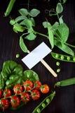 Οι ντομάτες κερασιών, chard και τα πράσινα μπιζέλια πλαισιώνουν μια κενή κάρτα στη μέση Στοκ εικόνα με δικαίωμα ελεύθερης χρήσης