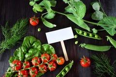 Οι ντομάτες κερασιών, chard και τα πράσινα μπιζέλια πλαισιώνουν μια κενή κάρτα στη μέση Στοκ φωτογραφία με δικαίωμα ελεύθερης χρήσης