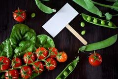 Οι ντομάτες κερασιών, chard και τα πράσινα μπιζέλια πλαισιώνουν μια κενή κάρτα στη μέση Στοκ φωτογραφίες με δικαίωμα ελεύθερης χρήσης