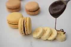 Οι νωποί καρποί της μπανάνας με τη σάλτσα σοκολάτας έχυσαν επάνω με τα μπισκότα κουταλιών και macaroon στοκ φωτογραφία με δικαίωμα ελεύθερης χρήσης