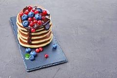 Οι νόστιμες σπιτικές τηγανίτες προγευμάτων με τη φρέσκια κρέμα βακκινίων, των βακκίνιων και σοκολάτας στη μαύρη πλάκα επιβιβάζοντ Στοκ Εικόνες