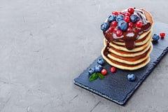 Οι νόστιμες σπιτικές τηγανίτες προγευμάτων με τη φρέσκια κρέμα βακκινίων, των βακκίνιων και σοκολάτας στη μαύρη πλάκα επιβιβάζοντ Στοκ φωτογραφία με δικαίωμα ελεύθερης χρήσης