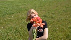 Οι ξανθές μυρωδιές μια ανθοδέσμη των τουλιπών Κορίτσι με μια ανθοδέσμη των λουλουδιών τουλιπών απόθεμα βίντεο