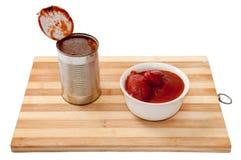 Οι ξεφλουδισμένες ντομάτες σε ένα άσπρα κύπελλο και ένα μέταλλο μπορούν Στοκ φωτογραφία με δικαίωμα ελεύθερης χρήσης