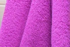Οι ξηρές πετσέτες λουτρών είναι πορφυρές στο λουτρό Στοκ Εικόνες