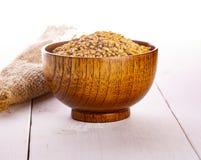 Οι ξηροί σπόροι σίτου, σιτάρια στο ξύλινο κύπελλο στοκ εικόνα