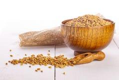 Οι ξηροί σπόροι σίτου, σιτάρια στο ξύλινο κύπελλο στοκ φωτογραφίες