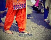 οι ξυπόλυτες γυναίκες με τα ζωηρόχρωμα ενδύματα σκουπίζουν το δρόμο ασφάλτου dur στοκ εικόνες με δικαίωμα ελεύθερης χρήσης