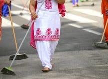οι ξυπόλυτες γυναίκες με τα ζωηρόχρωμα ενδύματα σκουπίζουν το δρόμο ασφάλτου στοκ φωτογραφίες με δικαίωμα ελεύθερης χρήσης