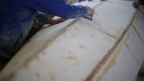 Οι ξυλουργοί γυαλίζουν μια ξύλινη βάρκα στο ναυπηγείο φιλμ μικρού μήκους