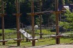 Οι ξύλινοι στυλοβάτες και τα κρεμώντας σχοινιά ενός σχοινιού σταθμεύουν στο υπόβαθρο του πράσινου δάσους Carpathians Ουκρανία στοκ φωτογραφία