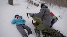 Οι οδοιπόροι ανοίγουν το φορείο στο δάσος στη χειμερινή ημέρα, η τραυματισμένη γυναίκα βρίσκεται στο χιόνι, πρώτες βοήθειες απόθεμα βίντεο