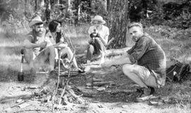 Οι οδοιπόροι κάθονται κοντά στην πυρά προσκόπων χαλαρώνοντας ενώ ψήνοντας τρόφιμα αναμονής Οι οδοιπόροι οργάνωσαν το γρήγορο πικ- στοκ εικόνα