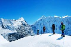 Οι οδοιπόροι με τα σακίδια πλάτης φθάνουν στην κορυφή της αιχμής βουνών Ελευθερία επιτυχίας και επίτευγμα ευτυχίας στα βουνά ενερ στοκ εικόνα