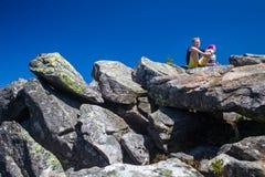 Οι οδοιπόροι στηρίζονται στην πέτρα πεζοποριεις Στοκ Εικόνες