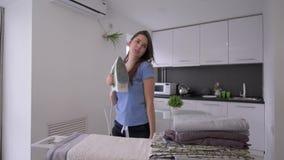 Οι οικιακές μικροδουλειές, αστεία γυναίκα οικονόμων με το σίδηρο λειαίνουν το ύφασμα στο σιδέρωμα του πίνακα και της διασκέδασης  απόθεμα βίντεο