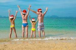 Οι οικογενειακές διακοπές στα Χριστούγεννα και τις νέες διακοπές έτους, οι ευτυχείς γονείς και τα παιδιά στα καπέλα santa έχουν τ Στοκ Φωτογραφία