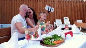 Οι οικογενειακές φωτογραφίες κάνουν το κινητό τηλέφωνο τοποθετούνται σε ένα selfi ραβδιών, εύθυμοι γονείς συλλογών με τα παιδιά,  απόθεμα βίντεο