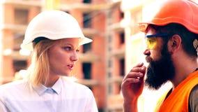Οι οικοδόμοι επικοινωνούν στο εργοτάξιο οικοδομής Μια γυναίκα σε ένα άσπρο κράνος επικοινωνεί με έναν γενειοφόρο άνδρα σε ένα πορ φιλμ μικρού μήκους