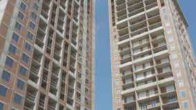 Οι οικοδόμοι πολυόροφων κτιρίων εργάζονται σε ένα ανασταλμένο λίκνο σε μια πρόσοψη της οικοδόμησης απόθεμα βίντεο