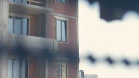 Οι οικοδόμοι πολυόροφων κτιρίων εργάζονται σε ένα ανασταλμένο λίκνο σε μια πρόσοψη της οικοδόμησης Κινηματογράφηση σε πρώτο πλάνο απόθεμα βίντεο