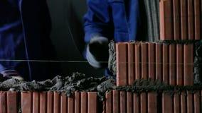Οι οικοδόμοι βάζουν τα τούβλα σε ένα εργοτάξιο οικοδομής απόθεμα βίντεο