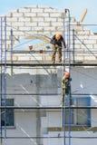 Οι οικοδόμοι εργαζομένων ανυψώνουν τα οικοδομικά υλικά στα υλικά σκαλωσιάς στοκ φωτογραφία με δικαίωμα ελεύθερης χρήσης