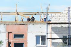 Οι οικοδόμοι εργαζομένων κάνουν την εγκατάσταση των υλικών σκαλωσιάς στοκ φωτογραφίες