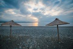 Οι ομπρέλες με μια στέγη καλάμων στέκονται στην παραλία θαλασσίως στην αυγή Στοκ Εικόνες