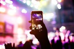 Οι οπαδοί μουσικής παίρνουν την εικόνα της σκηνής στη συναυλία στο smartphone στοκ φωτογραφία