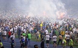 Οι οπαδοί ποδοσφαίρου τρέχουν έξω στην πίσσα Στοκ Εικόνες