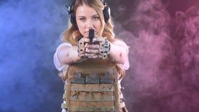 Οι οπλισμένοι ξανθοί βλαστοί γυναικών με το πυροβόλο όπλο σε έναν στόχο στο σκοτάδι με τον καπνό καλύπτουν o απόθεμα βίντεο