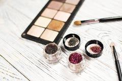 Οι ουδέτερες σκιές ματιών, χρωστικές ουσίες, ακτινοβολούν, βούρτσες και eyeliner Στοκ Φωτογραφία