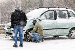 Οι οδηγοί προσπαθούν να εγκαταστήσουν τις αλυσίδες στα ελαστικά αυτοκινήτου τους κάτω από βαρύ Στοκ φωτογραφία με δικαίωμα ελεύθερης χρήσης