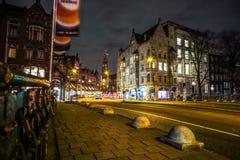 Οι οδοί νύχτας πόλεων του Άμστερνταμ με τη διαφορετική κίνηση ειδών μεταφέρουν & σκιαγραφίες των περαστικών Στοκ Φωτογραφία