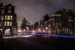 Οι οδοί νύχτας πόλεων του Άμστερνταμ με τη διαφορετική κίνηση ειδών μεταφέρουν & σκιαγραφίες των περαστικών Στοκ Εικόνες