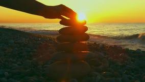 Οι πέτρες πυραμίδων στο θηλυκό χέρι ηλιοβασιλέματος θάλασσας υποβάθρου βάζουν μια μικρή πέτρα πάνω από μια πυραμίδα των πετρών απόθεμα βίντεο