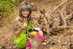 Οι πίθηκοι περιέβαλαν έναν ευτυχή τουρίστα που τους ταΐζει με τα φρούτα στοκ εικόνα με δικαίωμα ελεύθερης χρήσης