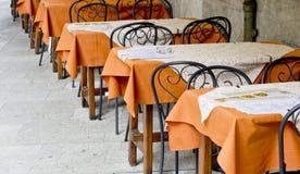 Οι πίνακες καλύπτονται με τα πορτοκαλιά τραπεζομάντιλα σε έναν υπαίθριο καφέ στοκ φωτογραφίες